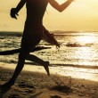 Silhouette of woman running along shore of ocean — Stock Photo
