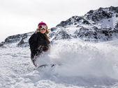 Woman snowboarder in motion in mountains — Stock Photo