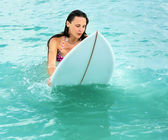 Attractive Young girl on surfboard in ocean — Stock Photo