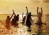 Silhouettes of people jumping in ocean — Stock Photo