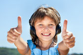 Little girl in headphones listens to music — Stock Photo