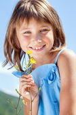 Happy little girl with a flower in his hand — Stock Photo
