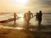 Silhouettes of friends running out of the ocean — ストック写真