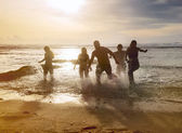 Silhouettes of friends running out of the ocean — Stock Photo