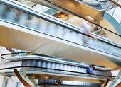 People in motion in escalators — Stockfoto