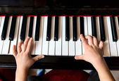 Child's hands playing the piano — Stock Photo