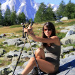Hiker girl on a stone with mountain walking sticks — Stock Photo