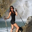Hiking model poses under waterfall — Stock Photo