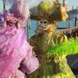 Two venetian mask in pink and green dress - Stock Photo
