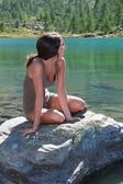 高山湖で石の上に魅力的な女の子のポーズ — ストック写真