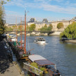 Seine river docks and boats with Louvre Museum in bakground - Stock Photo