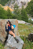 Trekking girl on a mountain rock relaxing — Stock Photo