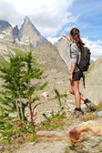 Trekking girl on high mountain trail pointing at the Aiguille No — Stock Photo