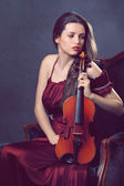 Beautiful girl posing with a fiddle — Stock Photo