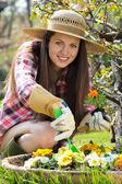 Krásná mladá žena usměje na fotoaparát s květem v ruce — Stock fotografie