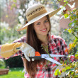 Attractive woman with pruning hook smiles - Stock Photo