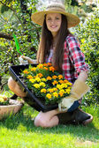 Young gardener and her new flowers — Stock Photo
