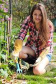 Usměvavá mladá žena pracuje v zahradě — Stock fotografie