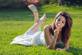 Attractive young girl with daisy lying on grass — Stock Photo