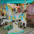 Detail of a carousel with white horses — Stock Photo