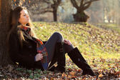 Girl relaxing in autumn light at the park — Stock Photo
