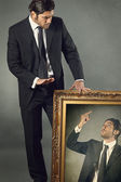 Elegant businessman and his angry paint — Stock Photo