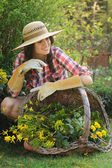 Beautiful gardener posing with wicker basket full of flower — Stock Photo