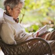 Mature lady reading and relaxing outdoors — Stock Photo