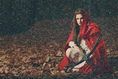Little red riding hood in the dark forest — Stock Photo