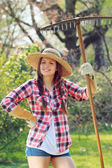 Smiling woman poses with a rake — Stock Photo