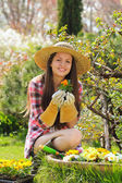 Belle giardiniere sorride con fiore in mano — Foto Stock