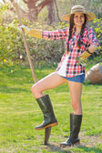 Beautiful smiling girl poses with a shovel in a garden — ストック写真