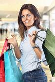 Shopping donna sorride al grande magazzino — Foto Stock