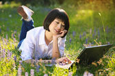 Attractive asian girl using laptop among flowers — Stock Photo