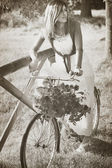 Vintage portrait of a young woman on a bike — Stock Photo