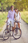 Funny young couple with bicycles — Stock Photo
