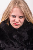 Cocky angry young cute young woman in fur jacket — Stock Photo