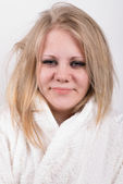Tired young cute woman in bathrobe — Stock Photo
