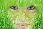 Uśmiechający się młoda kobieta, która wchłania się przez trawy — Zdjęcie stockowe