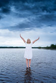 Young woman standing on a lake with a powerful storm behind her — Stock Photo