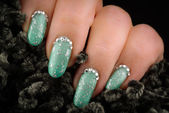 Green nails with glitter and rhinestones — Stock Photo