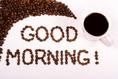 Good morning written in the coffee beans with a filled coffee cu — Stock Photo