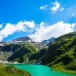 Turquoise lake with green hills around and the snowy mountains i — Stock Photo #41413481