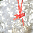 Stock Photo: Transparent Christmas ball hanging on red ribbon