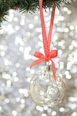 Transparent Christmas ball hanging on red ribbon — Stock Photo