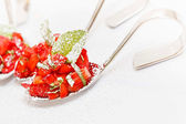 Strawberry salad mixed with sugar and mint, served on spoon — Stock Photo