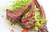 Costeletas de cordeiro assado com salada fresca ruccola — Fotografia Stock