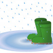Wellington boots in rain puddle — Stock Photo