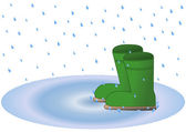 Wellington boots in rain puddle — Stock Photo