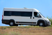 Minibus goes on country highway — Stock Photo
